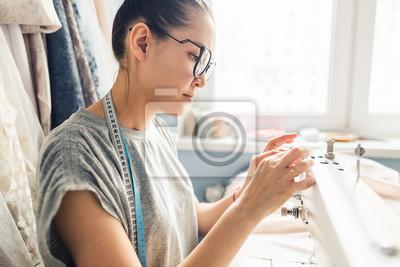 Bild Closeup Porträt der jungen Frau Näherin sitzen und näht auf Nähmaschine. Schneiderin arbeitet an der Nähmaschine. Schneider, ein Kleidungsstück an ihrem Arbeitsplatz zu machen. Hobby nähen als kleines