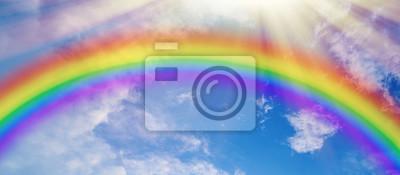 Bild Colorful rainbow and sun rays on blue cloudy sky