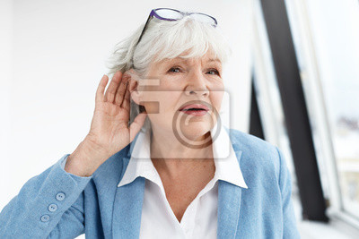 Bild Come again please? Attractive mature woman wearing blue jacket and spectacles on her head eavesdropping. Stylish retired female in elegant clothes holding hand at her ear, suffering from hearing loss