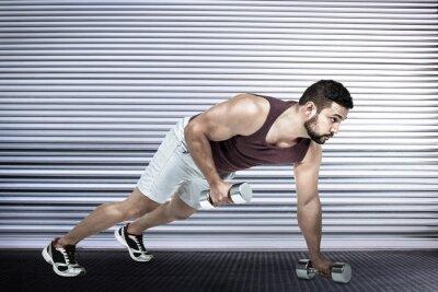 Composite-Bild der muskulösen Mann tun Push-ups mit Hanteln