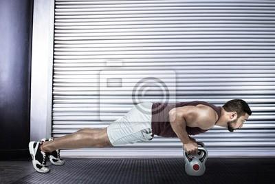 Composite-Bild der muskulösen Mann tun Push-ups mit Kettlebells