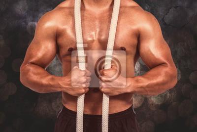 Composite-bild von muskulösen mann mit kampfseil