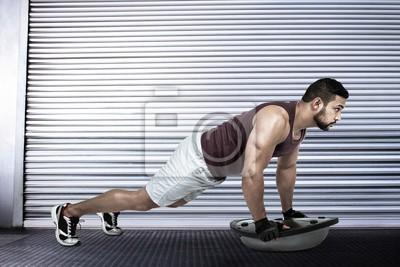 Composite-bild von muskulösen mann tun bosu push ups
