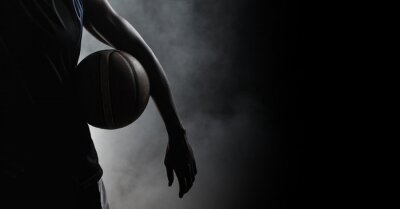 Bild Composition of athletic male basketball player over smoke on black background