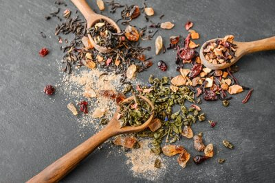 Bild Composition with different types of dry tea leaves and spoons on slate plate