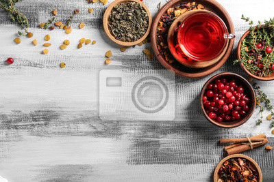 Bild Composition with glass cup of hot aromatic tea on wooden table