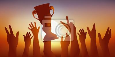 Concept du succès, avec une équipe de sportifs qui savourent leur victoire, en brandissant le trophée gagné lors d'une compétition sportive et en levant les bras en signe de la victoire.