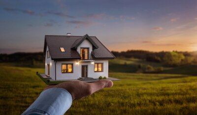 Bild Concept of buying or building new home. Male hand showing, offering a new dream house at the empty field with copy space