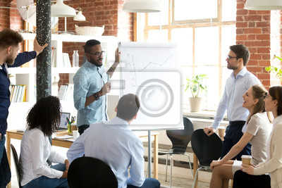 Bild Confident smiling African American business coach speaking presentation to colleagues group at briefing, company meeting, explaining growth of sales graph, reporting about good result, motivating
