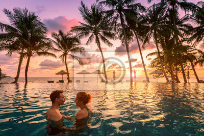 Bild Couple at beach vacation holidays resort relaxing in swimming pool with scenic tropical landscape at sunset, romantic summer honeymoon island destination, coconut palm tree near the sea