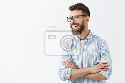 Bild Creative happy and funny bearded man with moustache in glasses with black rim turning left laughing out loud enjoying interesting and hilarious conversation holding hands crossed on chest relaxed