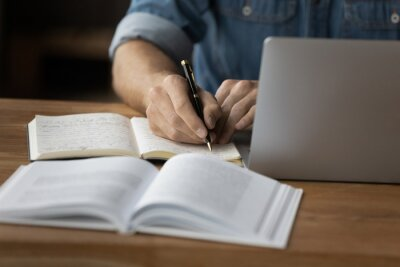 Bild Crop close up of male student make notes handwrite in notebook study online on computer from home. Man write in notepad talking distant on webcam virtual zoom call on laptop. Education concept.