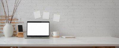 Bild Cropped shot of minimal workspace with mock-up laptop, smartphone, decorations and copy space