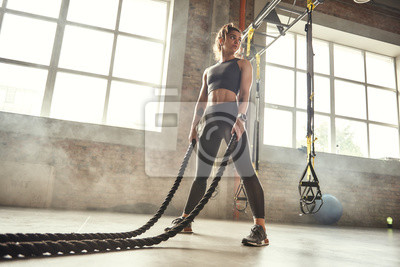 Bild CrossFit training. Young athletic woman with perfect body doing crossfit exercises with a rope in the gym.