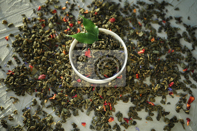 Bild Cup and heap of dry green tea leaves on table