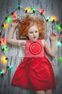 Bild Curly red-haired girl in a red dress lying with a garland