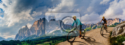 Bild Cycling woman and man riding on bikes in Dolomites mountains andscape. Couple cycling MTB enduro trail track. Outdoor sport activity.