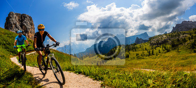 Bild Cycling woman and man riding on bikes in Dolomites mountains landscape. Couple cycling MTB enduro trail track. Outdoor sport activity.