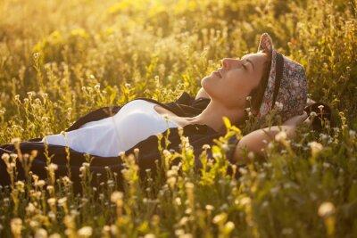 Bild Das Mädchen in einen Hut dremet inmitten von Wildblumen