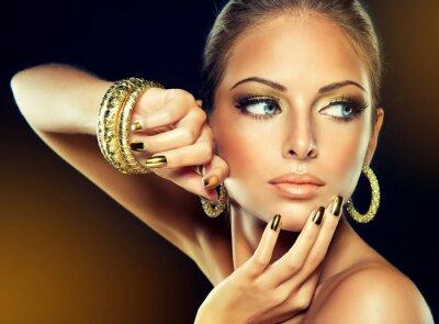 Bild Das Mädchen mit dem goldenen Make-up und Nägel aus Metall.