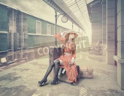 Bild Das Mädchen sitzt auf dem Koffer und wartet auf den Retro-Bahnhof. Vintage Farbe Karten Stil