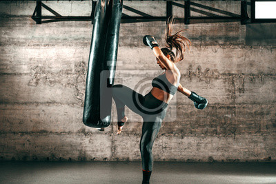 Bild Dedicated strong brunette with ponytail, in sportswear, bare foot and with boxing gloves kicking sack in gym.