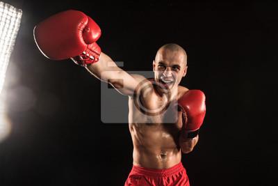Der junge Mann Kickboxen auf schwarz