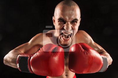 Der junge Mann Kickboxen auf schwarz mit schreienden Gesicht
