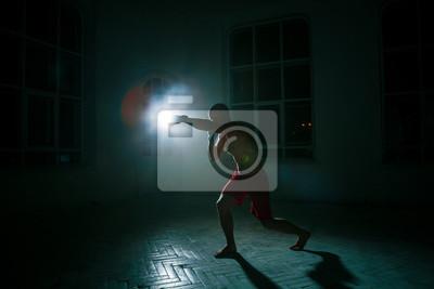 Der junge Mann Kickboxen auf schwarzem Hintergrund