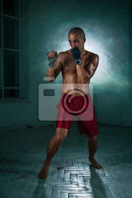 Der junge Mann Kickboxen in blauem Rauch
