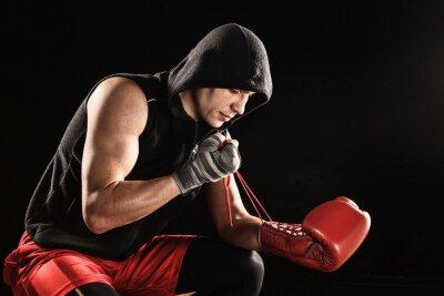 Der junge Mann Kickboxen Schnürung Handschuh