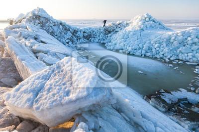 Der Mann schleicht sich an den gefrorenen Meereishügeln vorbei