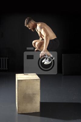 Der Mann springend auf Sitzkasten in der Turnhalle