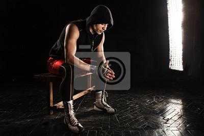 Der muskulöse Mann sitzt und ruht auf schwarz