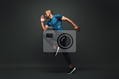 Bild Deserve Victory. Sportsman jumping over dark background, he is ready to run