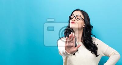 Bild Die junge Frau, die eine Ablehnung macht, werfen einen festen Hintergrund auf