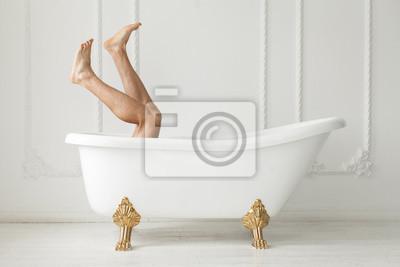 Die nackten Füße, die aus einem weißen Bad in einem weißen schauen