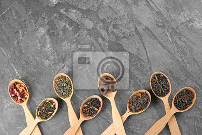 Bild Different sorts of tea in spoons on grey textured background, flat lay