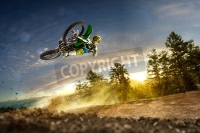 Bild Dirt Bike Fahrer fliegt hoch in den Abend