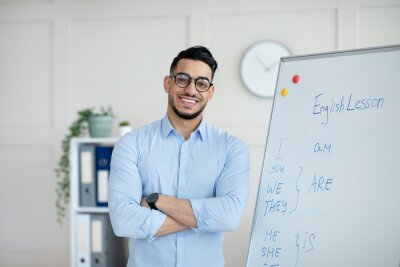 Bild Distance learning. Happy Arab male teacher giving online English class, standing with crossed arms near blackboard