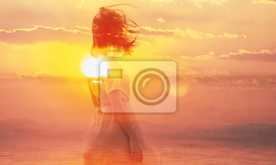 Bild Double exposure of young woman and sunset sky.