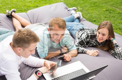 Bild Drei glückliche lächelnde junge Freunde, die draußen auf ein Kissen legen und Laptop betrachten.