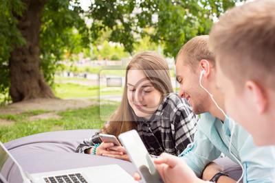 Bild Drei junge Freunde, die auf ein großes Kissen legen und draußen mit ihren Telefonen kühlen.