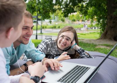 Bild Drei junge Freunde, die draußen auf ein Kissen legen, Kerle betrachten Mädchen.