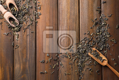 Bild Dry green tea leaves with scoops on wooden background