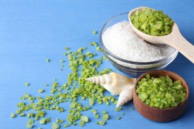 Bild Duftenden grünen und weißen Meersalz ist in einer Glasschale und hölzerne bowl.Scattered um das grüne Meersalz mit Muscheln auf einem blauen Holztisch mit Muscheln