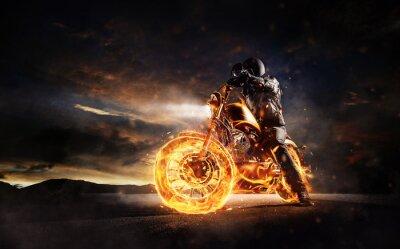 Bild Dunkles motorbiker, das auf brennendem Motorrad im Sonnenunterganglicht bleibt