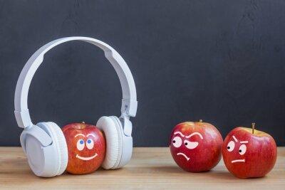 Bild Ein Apfel in den drahtlosen Kopfhörern, die Musik, Apfel zwei beneiden ihn hören. Musikkonzept. Psychologie der Einstellung