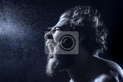 Bild Ein bärtiger Mann schreit wütend in einen Wasserstrahl gegen einen schwarzen Hintergrund. Getöntes Bild.