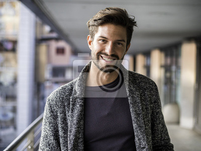 Bild Ein hübscher junger Mann in der städtischen Einstellung in der europäischen Stadt, Stellung und Lächeln zur Kamera glücklich